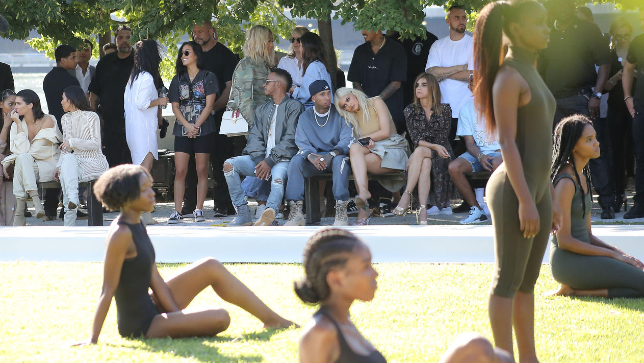Kim Kardashian and Kendall Jenner watch the Yeezy season 4 show in a park with other celebs and sisters as they watch the runway models. Kendall Jenner was spotted alongside Lewis Hamilton and Tyga as the group took in the sights of the show.